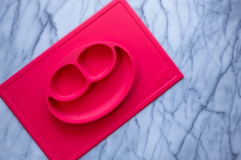 Searching for non-plastic baby dishes? Read why I love the ezpz happy mat for simplifying mealtime with toddlers. Made of silicone, this innovative all-in-one dish and placemat makes toddler meals simple and fun!